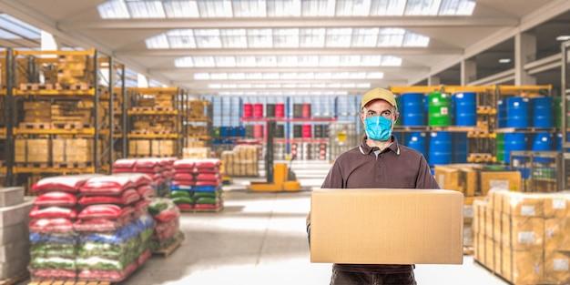 Man met masker en pakket, interieur van een industrieel pakhuis waar verschillende goederen zijn opgeslagen.