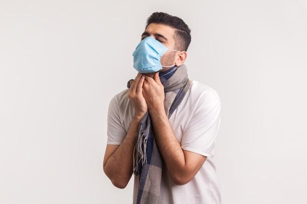 Man met masker en sjaal met keelpijn, hoesten en stikken, met symptomen van covid-19