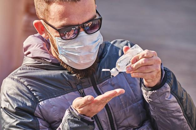 Man met masker gebruikt antibacteriële gel op handen