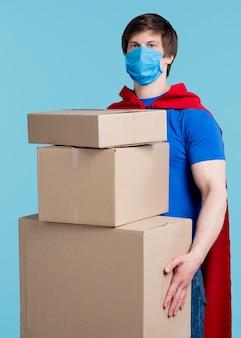 Man met masker houden van dozen