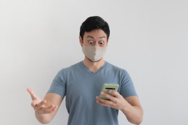 Man met masker is blij met de promotie in de smartphoneapplicatie.