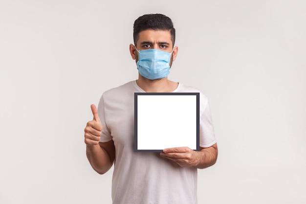 Man met masker met duim omhoog en met witte poster, mockup-sjabloon, ruimte voor waarschuwingsinformatie