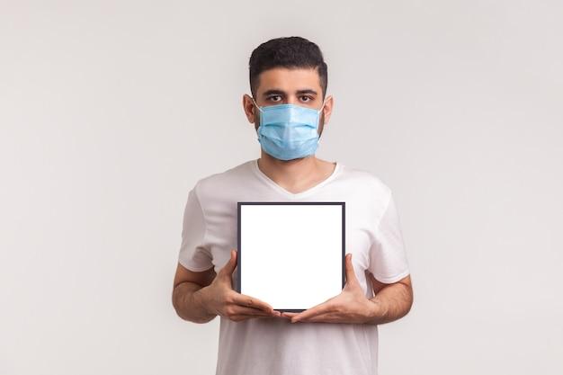 Man met masker met witte poster, mockup-sjabloon, ruimte voor informatie over coronavirusepidemie