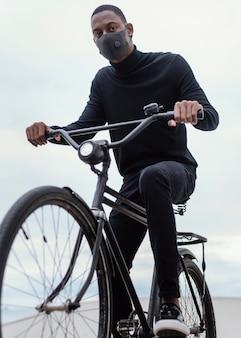 Man met masker rijden op zijn fiets in de stad
