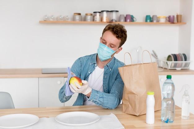 Man met masker schoonmaken fruit