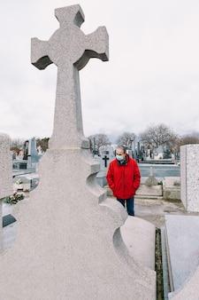 Man met masker, verdrietig en biddend, voor het graf van een overleden familielid in tijden van covid-19