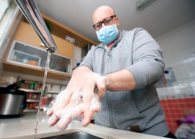 Man met masker wast handen in preventie tegen covid-19