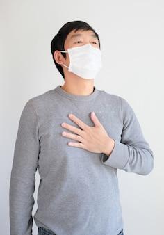 Man met masker wordt ziek van corona-virus, covid19-symptoom als niezen, hoesten, koorts, pijn in het lichaam, ademhaling, pijn.
