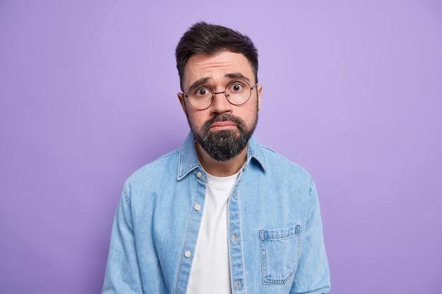 Man met medelijdende uitdrukking fronst gezicht ziet er ongelukkig uit wordt gehinderd gezichten problemen draagt ronde bril spijkerblouse