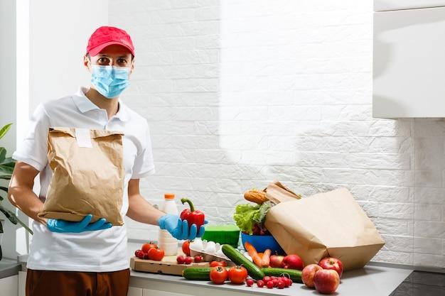 Man met medisch gezichtsmasker demonteert voedselzakken thuis. quarantaine. gezondheidsconcept. coronavirus. online bestellen van producten. producten aan huis leveren. bezorgservice