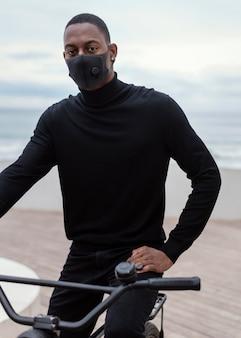 Man met medisch masker en zijn fiets rijden