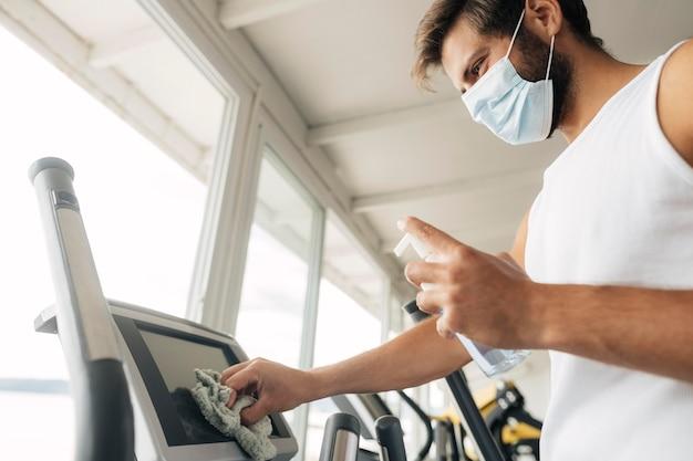 Man met medisch masker fitnessapparatuur desinfecteren