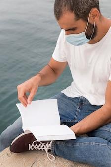 Man met medisch masker leesboek bij het meer