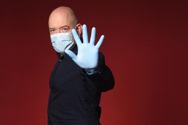 Man met medisch masker met stopbord op rode hebben