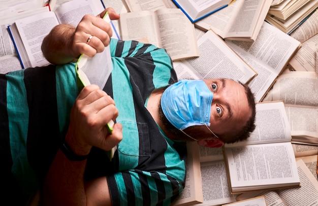 Man met medisch masker met veel papieren boeken