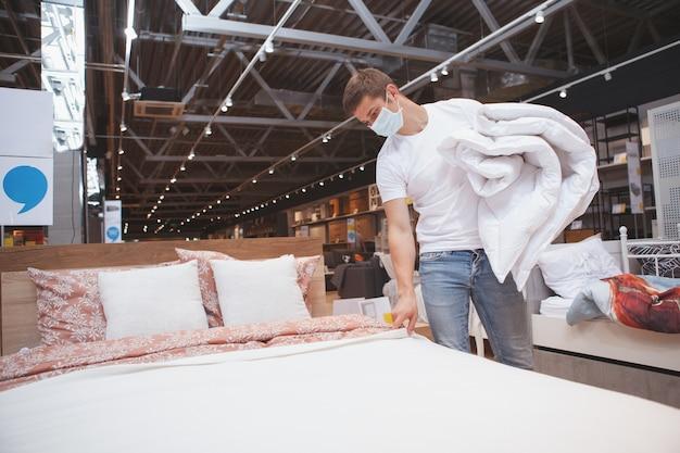 Man met medisch masker winkelen voor meubels tijdens coronavirus panemie