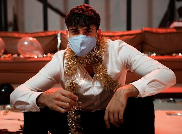 Man met medisch masker zittend op een oudejaarsavondfeestje