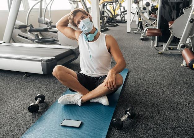 Man met medische masker en koptelefoon op de sportschool uit te werken op de mat