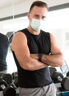 Man met medische masker poseren in de sportschool
