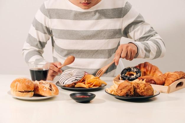 Man met meerdere soorten fastfood. ongezond voedselconcept