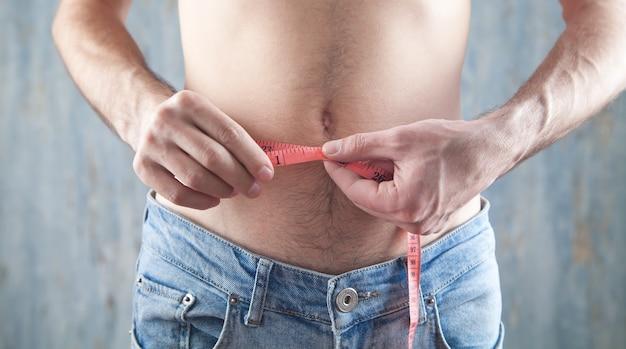 Man met meetlint. gewichtsverlies
