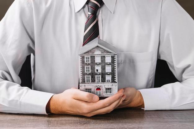 Man met miniatuur huis in handen