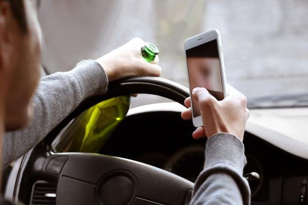 Man met mobiele telefoon en flesje bier tijdens het autorijden, close-up. drink niet en rijd niet concept