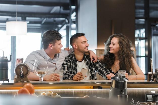 Man met mobiele telefoon genieten met vrienden in de bar