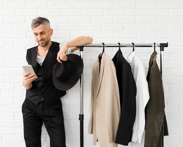 Man met mobiele telefoon naast kledingkast