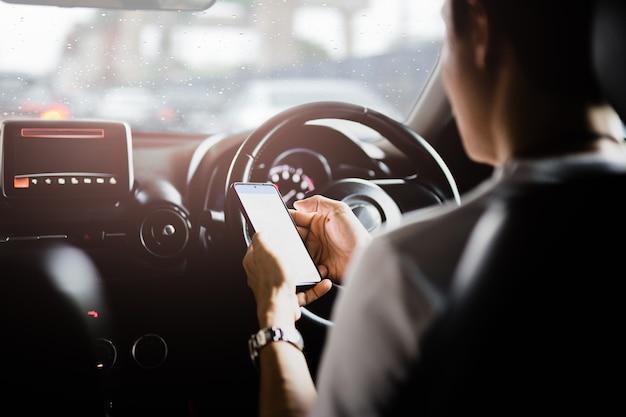 Man met mobiele telefoon tijdens het rijden op regenachtige dag