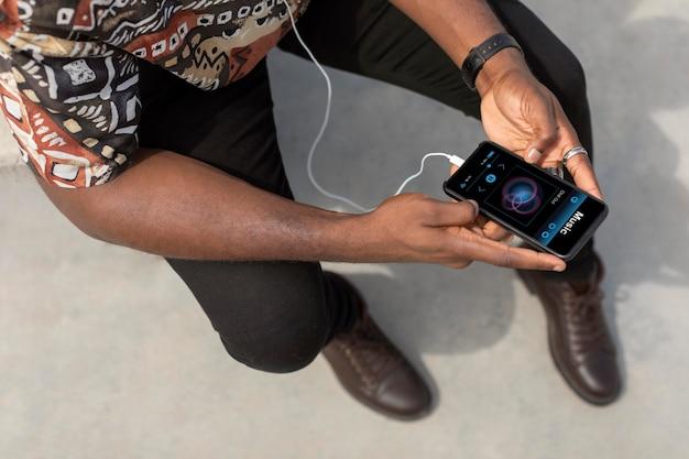 Man met moderne smartphone met koptelefoon