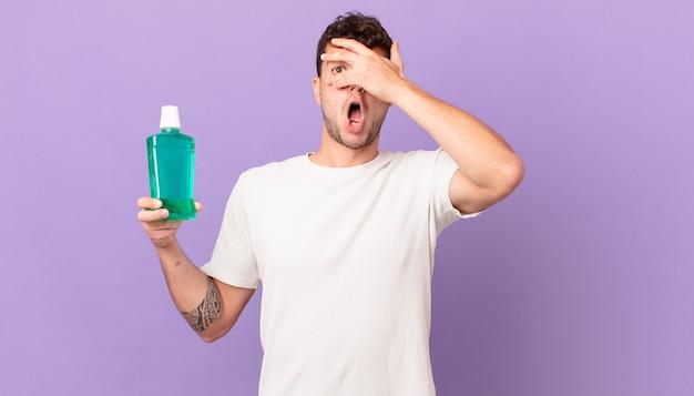 Man met mondwater die geschokt, bang of doodsbang kijkt, zijn gezicht bedekt met de hand en tussen de vingers gluurt