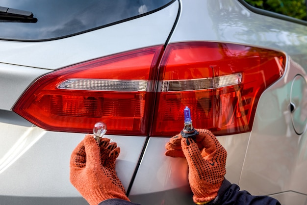 Man met nieuwe lampen in de buurt van autokoplampen