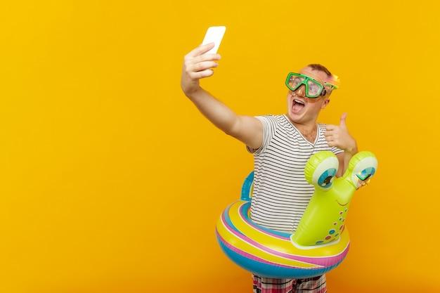 Man met onderwatermasker, gestreept shirt, baantjes zwemmen in de telefoon kijken, een selfie nemen