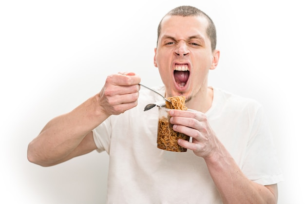 Man met open mond emotioneel fastfoodnoedels eten uit de doorzichtige plastic beker.