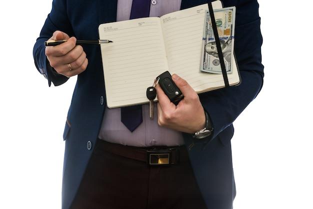 Man met open notebook ondertekent koop- of leaseovereenkomst met contant geld geïsoleerd op een witte muur.