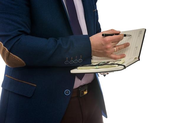 Man met open notebook tekent aankoop- of leaseovereenkomst met geïsoleerd contant geld.
