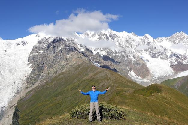 Man met opgeheven handen die zich op besneeuwde bergen bevinden