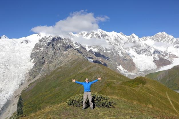 Man met opgeheven handen staande op de besneeuwde bergen