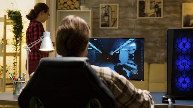 Man met opgeheven handen vieren overwinning op videogames zittend op gaming stoel.