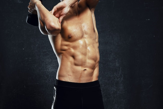 Man met opgepompt gespierd lichaam workout oefening sportschool donkere achtergrond