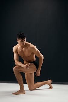 Man met opgepompt lichaam in donker slipje studiomodel