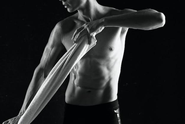 Man met opgepompte buikspieren oefeningen motivatie donkere achtergrond