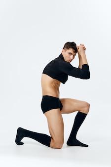Man met opgepompte spieren staat op zijn knie op een lichte achtergrond