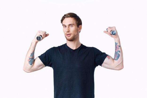 Man met opgepompte spieren van armen en halters zwarte tshirt witte achtergrond