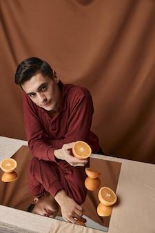 Man met oranje sinaasappelen op een stoffenachtergrond en modelbezinning in de spiegel