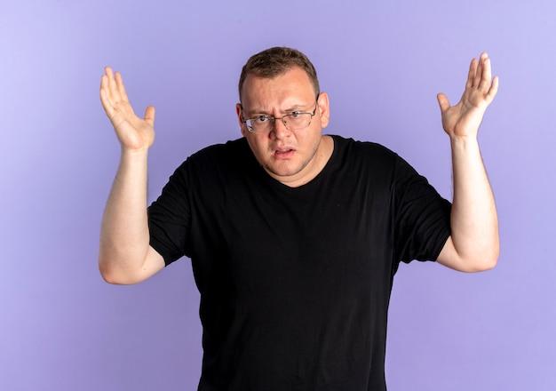 Man met overgewicht in bril die zwart t-shirt draagt en die verward en ontevreden kijkt met opgeheven armen als vragen of ruzie staande over blauwe muur