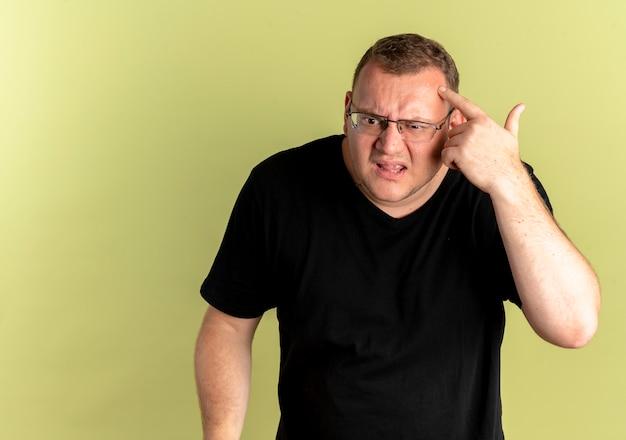 Man met overgewicht in glazen met een zwart t-shirt die met wijsvinger naar zijn slaap wijst en verward kijkt terwijl hij zich probeert te herinneren dat hij over de lichte muur stond