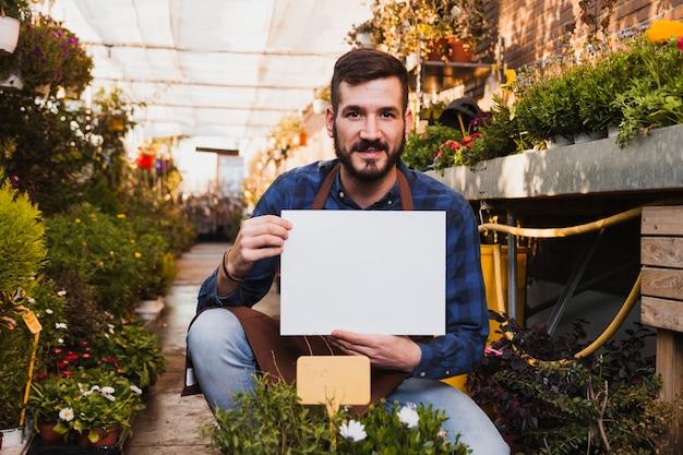 Man met papieren blad in de buurt van bloemen
