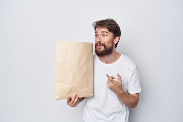 Man met papieren zak in handen mockup winkelen emoties lichte achtergrond